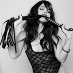 A woman in lace lingerie with a flogger in her mouth.